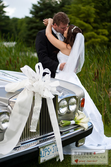 Bride and Groom Kissing by the Wedding Car
